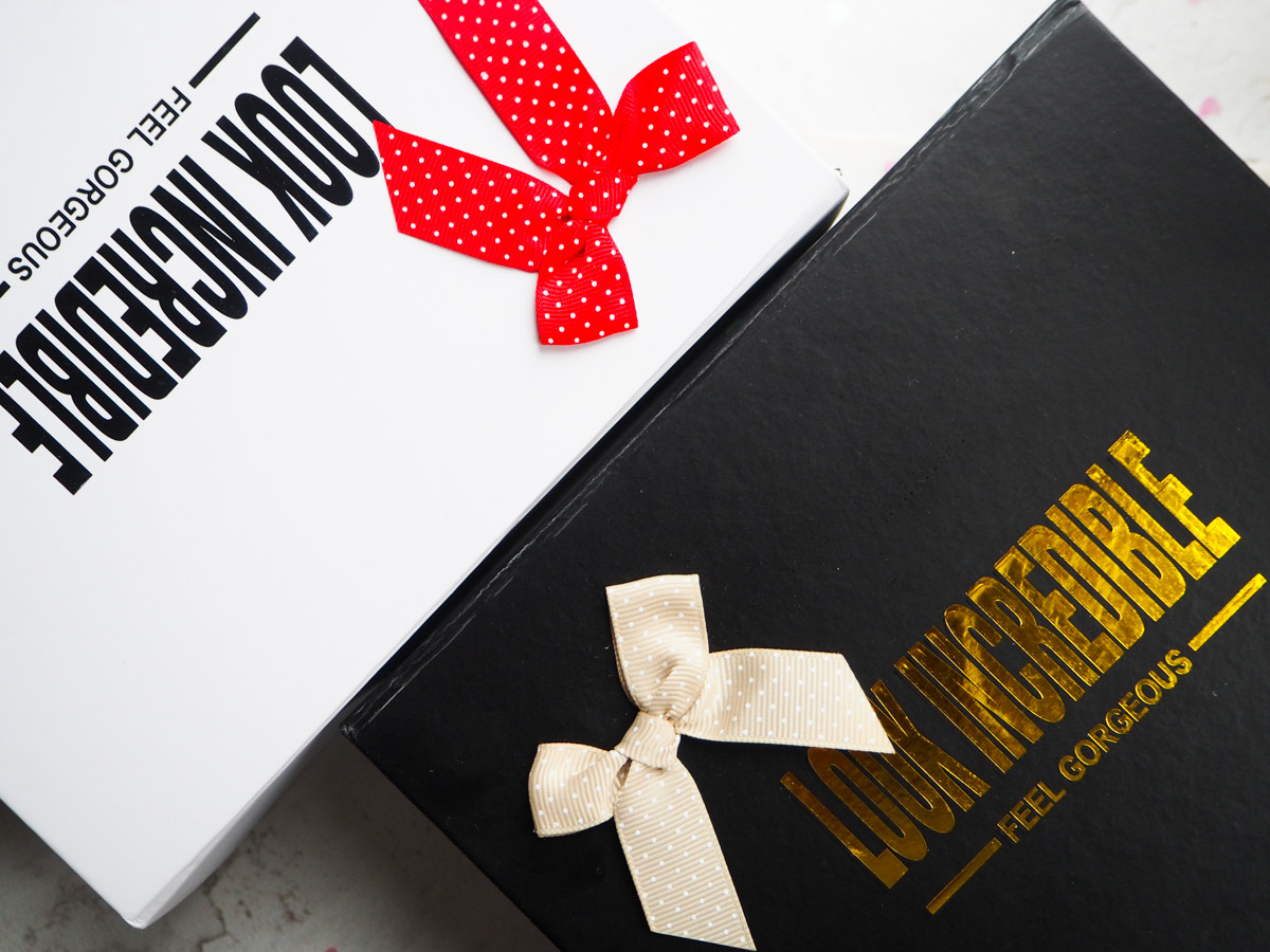 Deluxe Box is White with Red Bow, Standard Box is black and gold (more deluxe?) with a beige bow